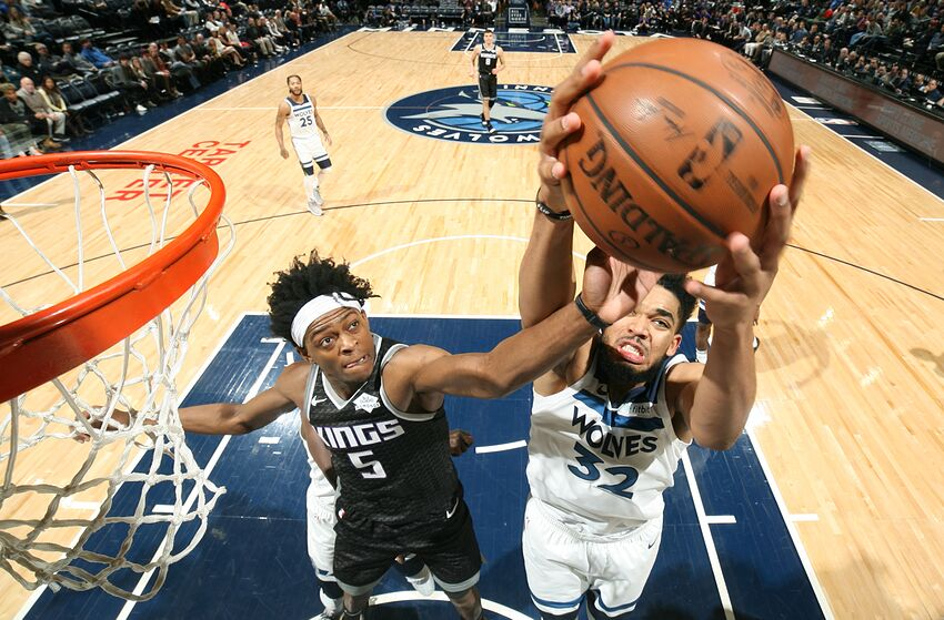 MINNEAPOLIS, MN - FEBRUARY 25: De'Aaron Fox #5 of the Sacramento Kings and Karl-Anthony Towns #32 of the Minnesota Timberwolves looks to grab the rebound on February 25, 2019 at Target Center in Minneapolis, Minnesota. NOTE TO USER: User expressly acknowledges and agrees that, by downloading and or using this Photograph, user is consenting to the terms and conditions of the Getty Images License Agreement. Mandatory Copyright Notice: Copyright 2019 NBAE (Photo by David Sherman/NBAE via Getty Images)