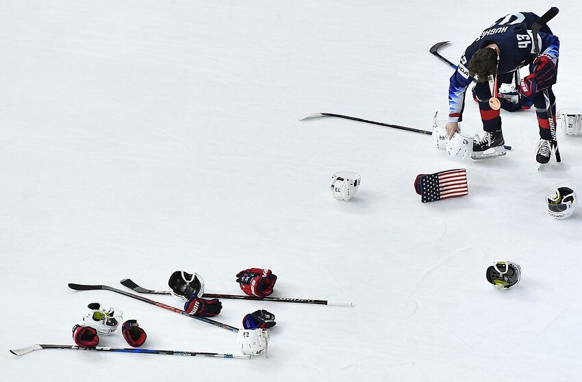 c89a22e03 Team USA's Quinn Hughes collects gear laying on the ice after the bronze  medal match USA