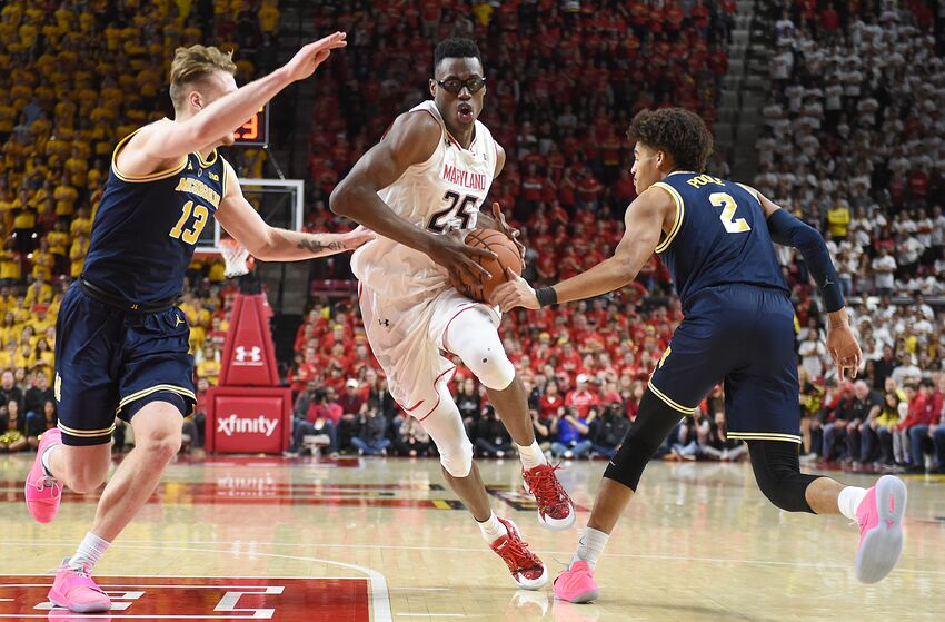 COLLEGE PARK, MD - MARCH 03: Jalen Smith #25 of the Maryland Terrapins drives to the basket through Ignas Brazdeikis #13 and Jordan Poole #2 of the Michigan Wolverines in the second half during a college basketball game against the Michigan Wolverines at the XFinity Center on March 3, 2019 in College Park, Maryland. (Photo by Mitchell Layton/Getty Images)
