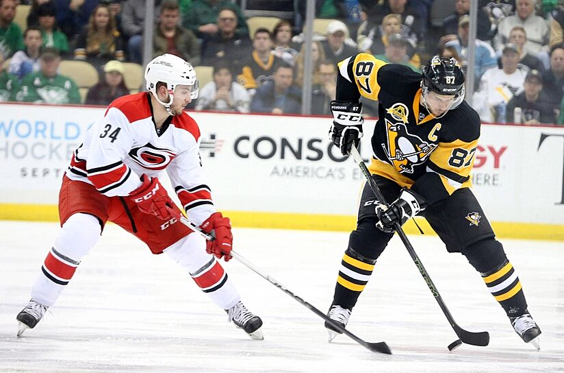 Mar 17, 2016; Pittsburgh, PA, USA; Pittsburgh Penguins center Sidney Crosby (87) moves the puck as Carolina Hurricanes left wing Phil Di Giuseppe (34) pressures during the second period at the CONSOL Energy Center. Mandatory Credit: Charles LeClaire-USA TODAY Sports