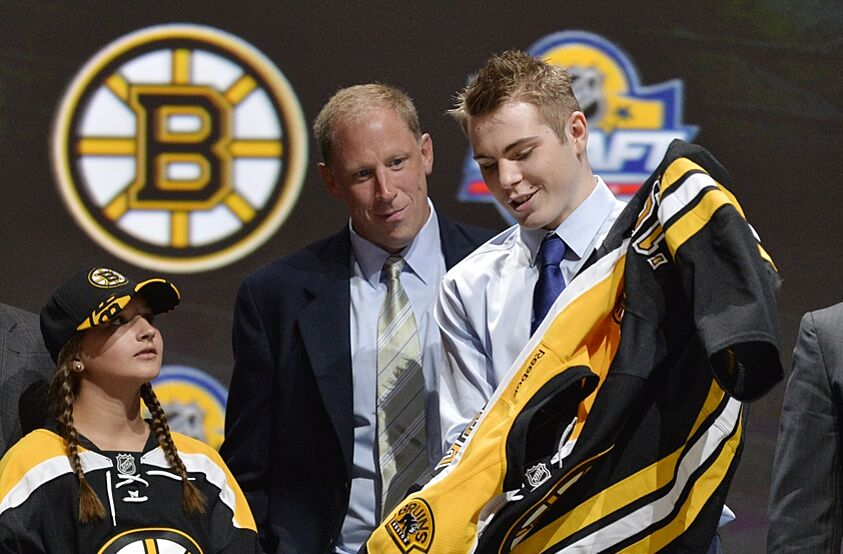 Jun 26, 2015; Sunrise, FL, USA; Jake Debrusk puts on a team jersey after being selected as the number fourteen overall pick to the Boston Bruins in the first round of the 2015 NHL Draft at BB&T Center. Mandatory Credit: Steve Mitchell-USA TODAY Sports
