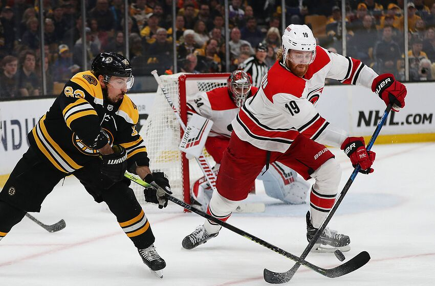 BOSTON - MAY 12: Boston Bruins' Brad Marchand (63) chases a loose puck in the first period with Carolina's Dougie Hamilton (19). The Boston Bruins host the Carolina Hurricanes in Game 2 of the NHL Eastern Conference Finals on May 12, 2019. (Photo by John Tlumacki/The Boston Globe via Getty Images)