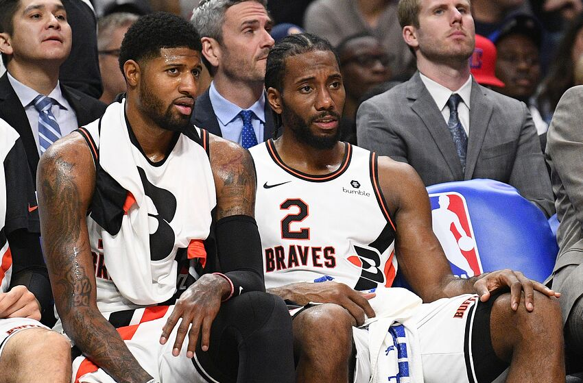 LOS ANGELES, CA - DECEMBER 03: Los Angeles Clippers Guard Paul George (13) and Los Angeles Clippers Forward Kawhi Leonard (2) look on from the bench during a NBA game between the Portland Trail Blazers and the Los Angeles Clippers on December 3, 2019 at STAPLES Center in Los Angeles, CA. (Photo by Brian Rothmuller/Icon Sportswire via Getty Images)