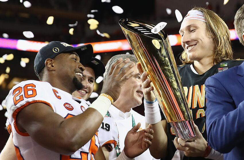 SANTA CLARA, CA - JANUARY 07: Adam Choice #26 and Trevor Lawrence #16 of the Clemson Tigers celebrate with the trophy after their teams 44-16 win over the Alabama Crimson Tide in the CFP National Championship presented by AT&T at Levi's Stadium on January 7, 2019 in Santa Clara, California. (Photo by Ezra Shaw/Getty Images)