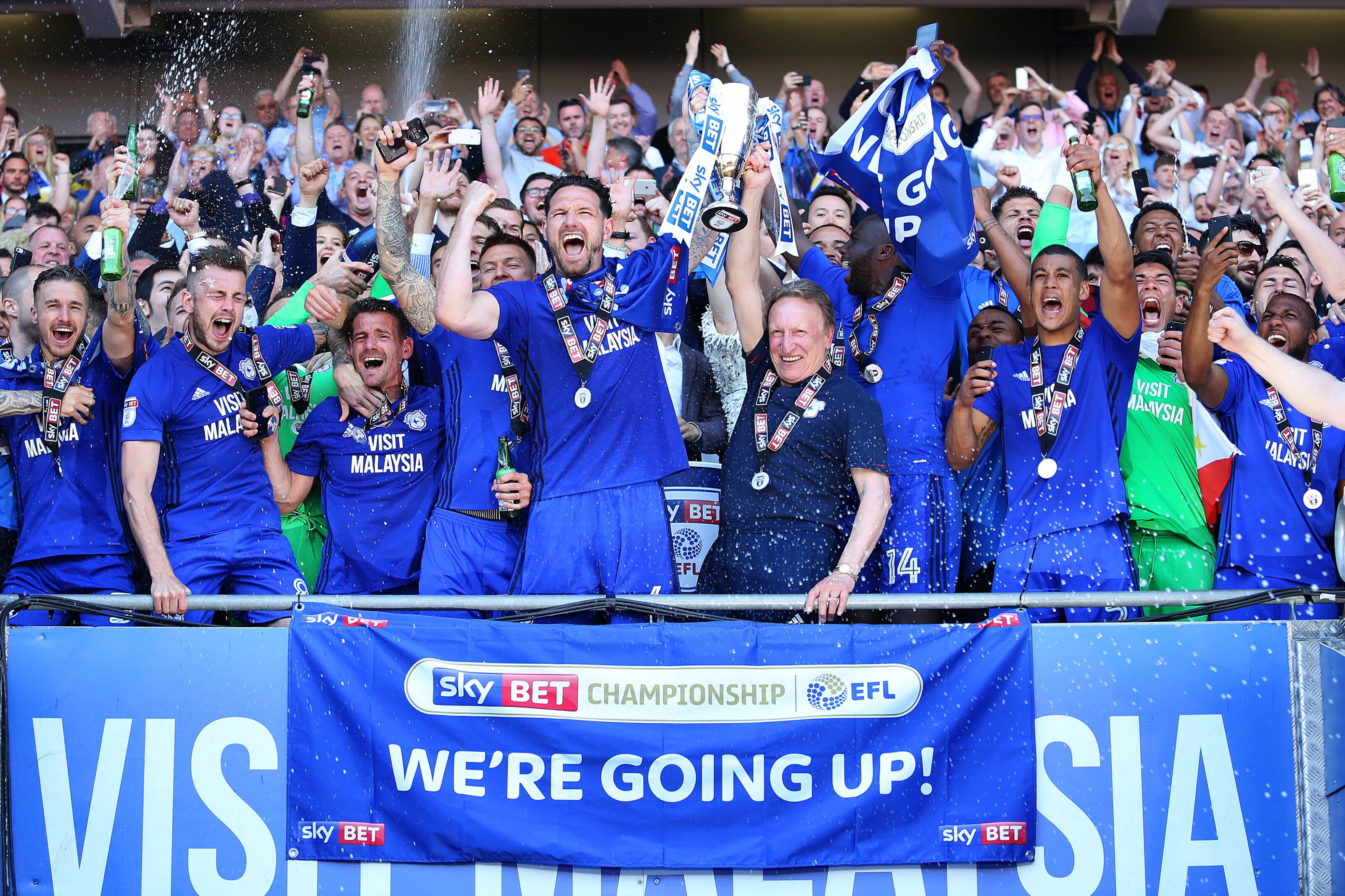CARDIFF, WALES - MAY 06: Sean Morrison of Cardiff City and Cardiff City manager Neil Warnock lift the trophy after being automatically promoted to the Premier League after the final whistle of the Sky Bet Championship match between Cardiff City and Reading at The Cardiff City Stadium on May 06, 2018 in Cardiff, Wales. (Photo by Athena Pictures/Getty Images)