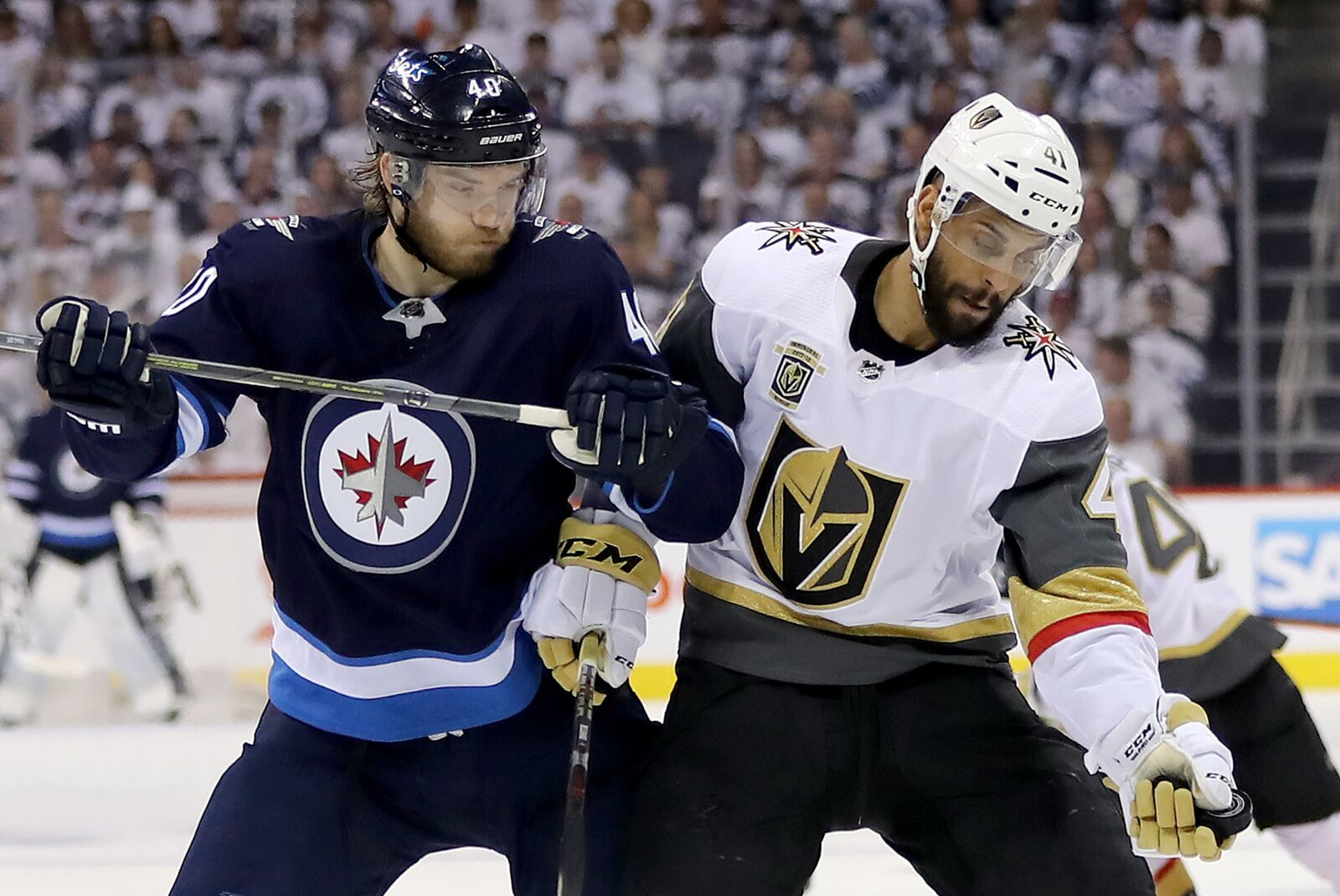 WINNIPEG, MB - MAY 12: Pierre-Edouard Bellemare #41 of the Vegas Golden Knights grabs the puck as Joel Armia #40 of the Winnipeg Jets defends in Game One of the Western Conference Finals during the 2018 NHL Stanley Cup Playoffs at Bell MTS Place on May 12, 2018 in Winnipeg, Canada. (Photo by Elsa/Getty Images)