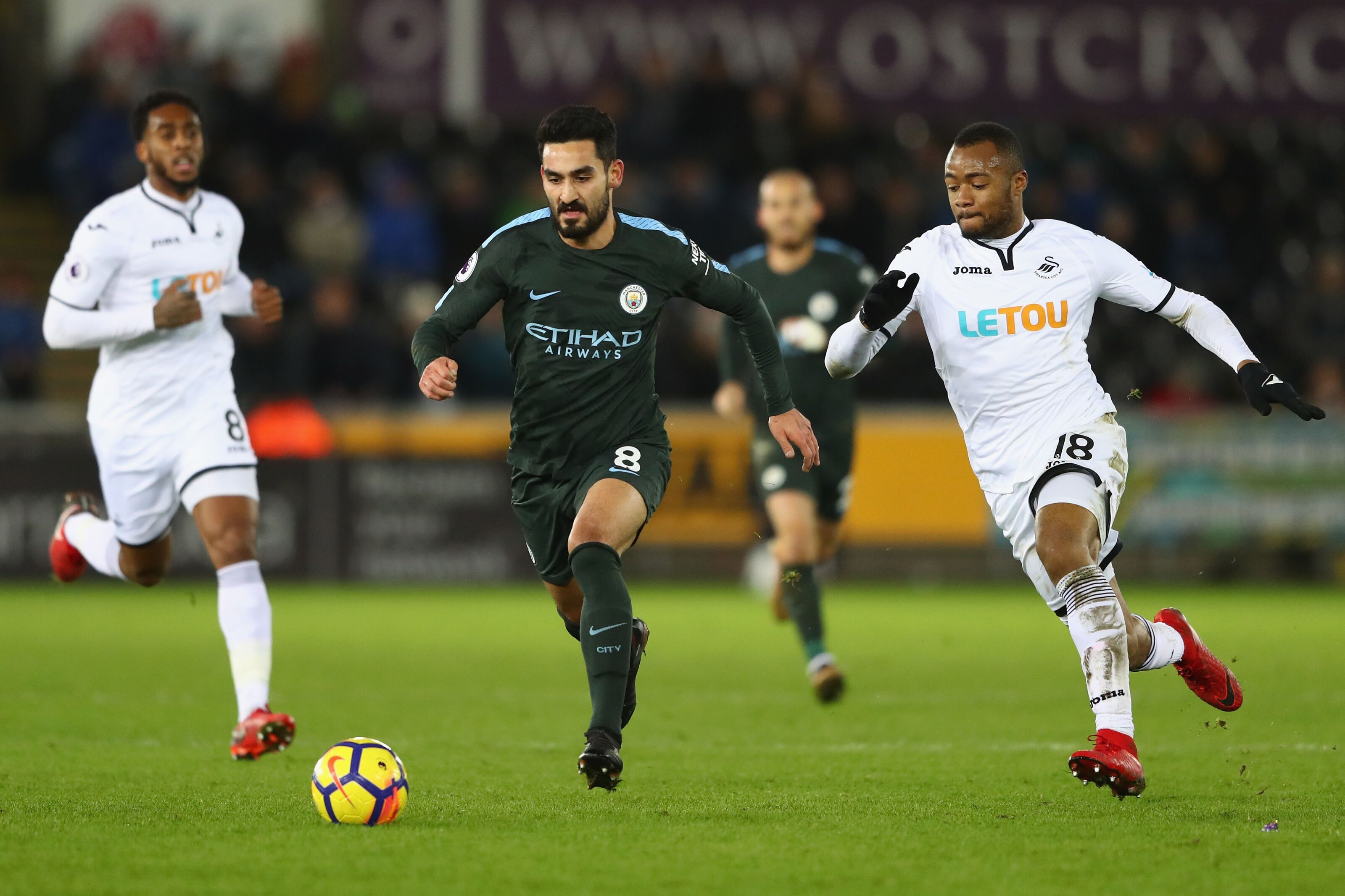 SWANSEA, WALES - DECEMBER 13: Ilkay Gundogan of Manchester City is tracked by Jordan Ayew of Swansea City during the Premier League match between Swansea City and Manchester City at Liberty Stadium on December 13, 2017 in Swansea, Wales. (Photo by Michael Steele/Getty Images)