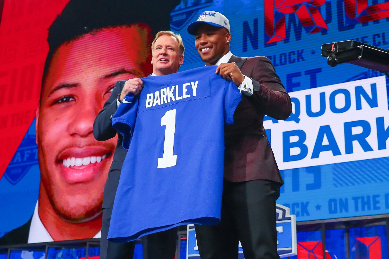 ARLINGTON, TX - APRIL 26: Saquon Barkley and NFL Commissioner Roger Goodell hold up a NY Giants jersey after being selected by the New York Giants with the 2nd pick during the First Round of the 2018 NFL Draft on April 26, 2018 at AT&T Stadium in Arlington Texas. ( Rich Graessle/Icon Sportswire via Getty Images)