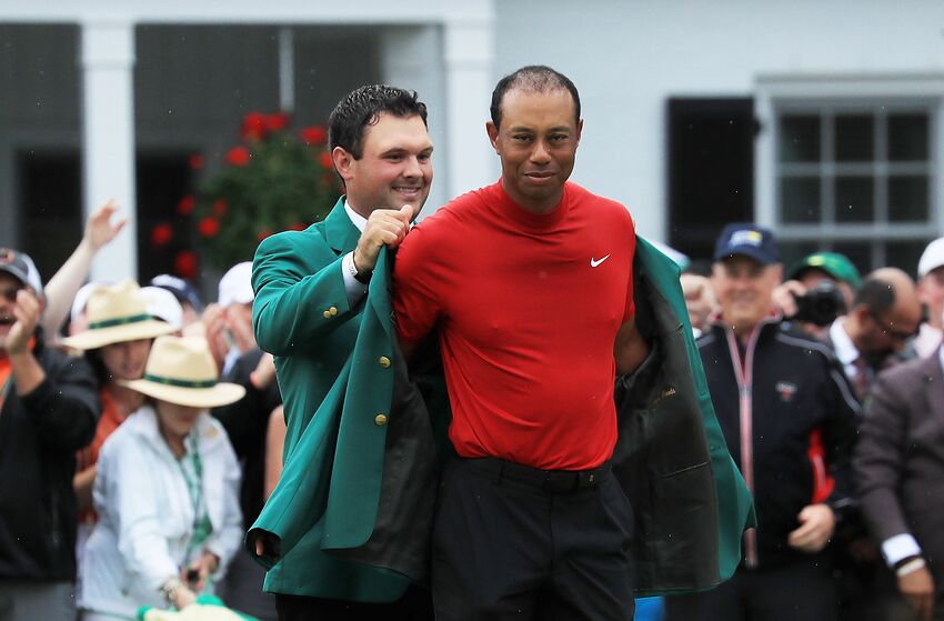 AUGUSTA, GEORGIA - APRIL 14: Tiger Woods (R) of the United States is awarded the Green Jacket by Masters champion Patrick Reed (L) during the Green Jacket Ceremony after winning the Masters at Augusta National Golf Club on April 14, 2019 in Augusta, Georgia. (Photo by David Cannon/Getty Images)