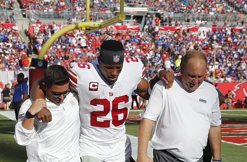 TAMPA, FLORIDA - SEPTEMBER 22: Running back Saquon Barkley #26 of the New York Giants is helped back to the locker room by medical staff after an injury during the game against the Tampa Bay Buccaneers at Raymond James Stadium on September 22, 2019 in Tampa, Florida. (Photo by Mike Zarrilli/Getty Images)