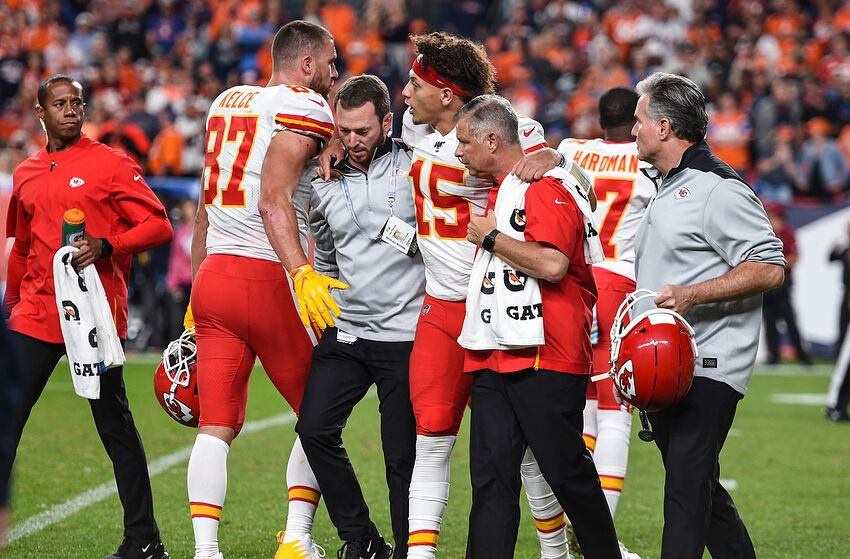Kansas City Chiefs quarterback Patrick Mahomes (15) comes off the field with the aid of trainers after he injured his knee in the second quarter against the Denver Broncos on Thursday, Oct. 17, 2019, at Empower Field at Mile High in Denver, Colo. Kansas City Chiefs tight end Travis Kelce (87) meets Mahomes as he came off the field. (Tammy Ljungblad/Kansas City Star/Tribune News Service via Getty Images)