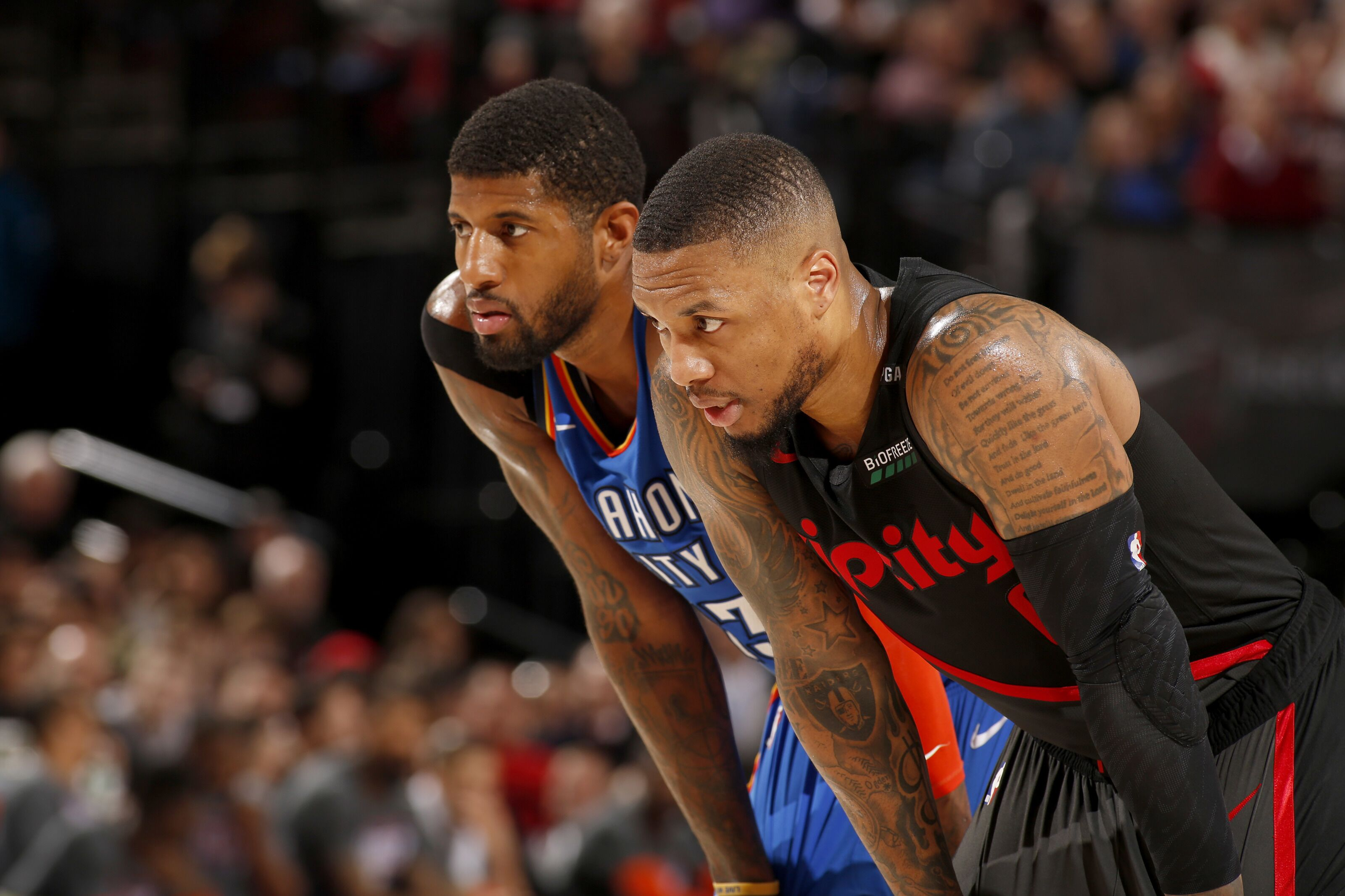 PORTLAND, OR - MARCH 7: Paul George #13 of the Oklahoma City Thunder and Damian Lillard #0 of the Portland Trail Blazers look on during the game on March 7, 2019 at the Moda Center Arena in Portland, Oregon. NOTE TO USER: User expressly acknowledges and agrees that, by downloading and or using this photograph, user is consenting to the terms and conditions of the Getty Images License Agreement. Mandatory Copyright Notice: Copyright 2019 NBAE (Photo by Cameron Browne/NBAE via Getty Images)