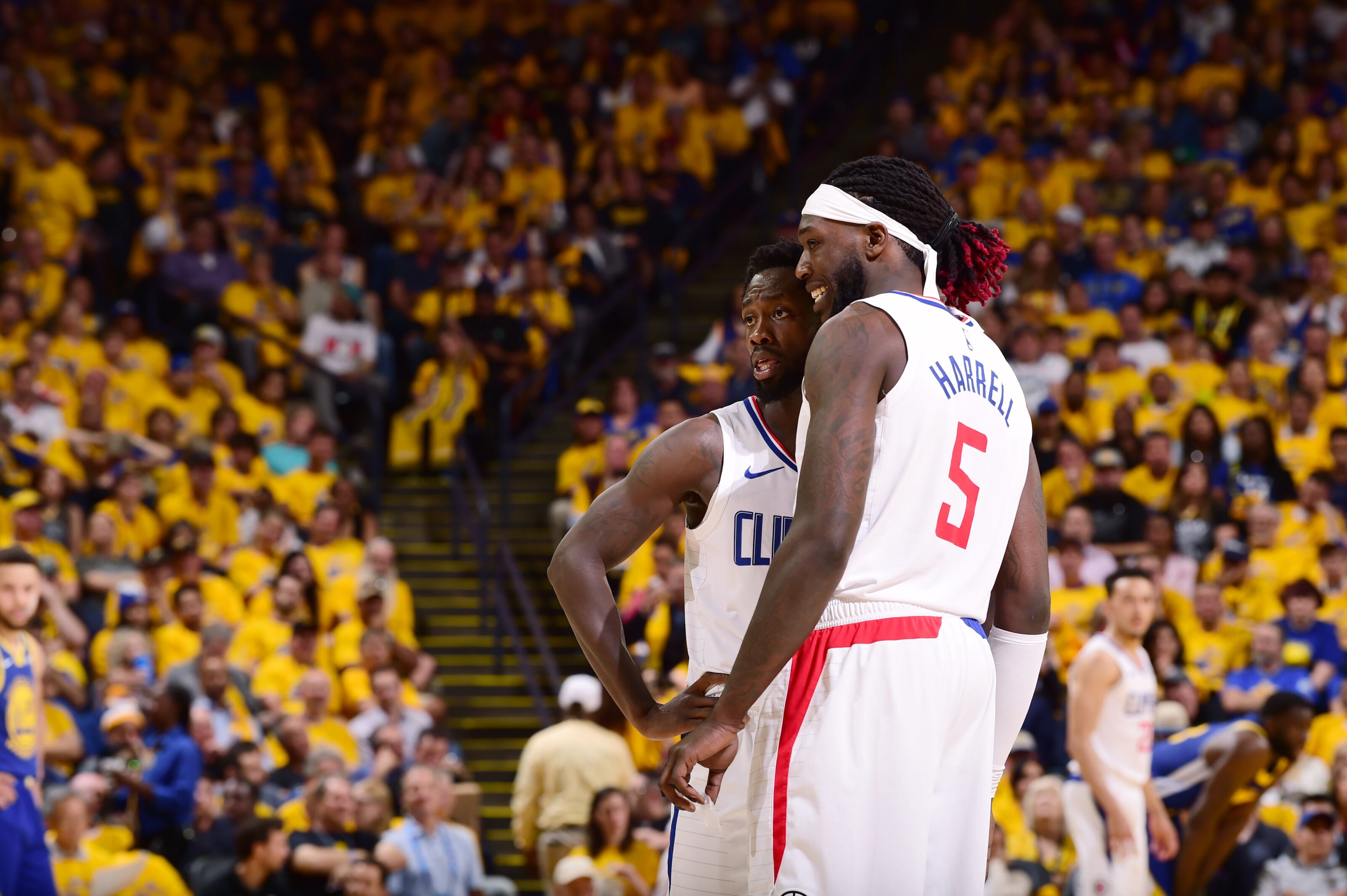 OAKLAND, CA - APRIL 24: Patrick Beverley #21 and Montrezl Harrell #5 of the LA Clippers talk during Game Five of Round One of the 2019 NBA Playoffs against the Golden State Warriors on April 24, 2019 at ORACLE Arena in Oakland, California. NOTE TO USER: User expressly acknowledges and agrees that, by downloading and/or using this photograph, user is consenting to the terms and conditions of Getty Images License Agreement. Mandatory Copyright Notice: Copyright 2019 NBAE (Photo by Noah Graham/NBAE via Getty Images)