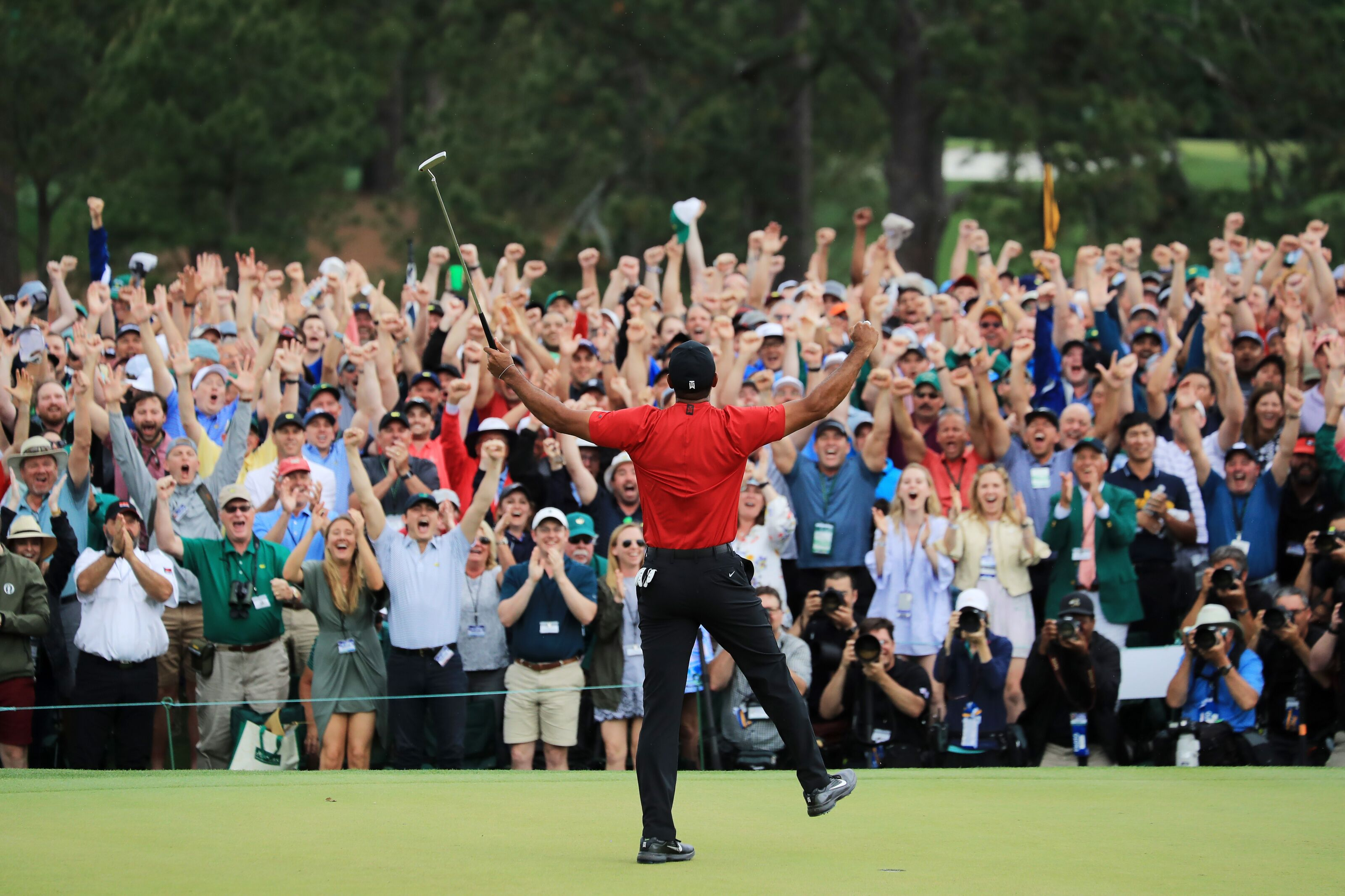 AUGUSTA, GEORGIA - APRIL 14: Patrons cheer as Tiger Woods of the United States celebrates after sinking his putt on the 18th green to win during the final round of the Masters at Augusta National Golf Club on April 14, 2019 in Augusta, Georgia. (Photo by David Cannon/Getty Images)