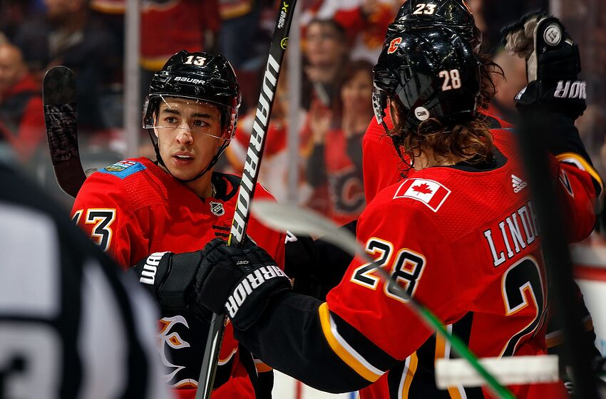 CALGARY, AB - MARCH 12: Johnny Gaudreau #13 and Elias Lindholm #28 of the Calgary Flames and teammates celebrate a goal against the New Jersey Devils during an NHL game on March 12, 2019 at the Scotiabank Saddledome in Calgary, Alberta, Canada. (Photo by Gerry Thomas/NHLI via Getty Images)