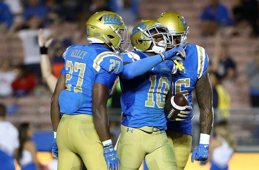 PASADENA, CA - OCTOBER 20: Demetric Felton #10 of the UCLA Bruins celebrates with teammates Joshua Kelley #27 and Devin Asiasi #86 after Felton scored a touchdown in the second half of the NCAA college football at the Rose Bowl on October 20, 2018 in Pasadena, California. The Bruins defeated the Wildcats 31-30. (Photo by Victor Decolongon/Getty Images)