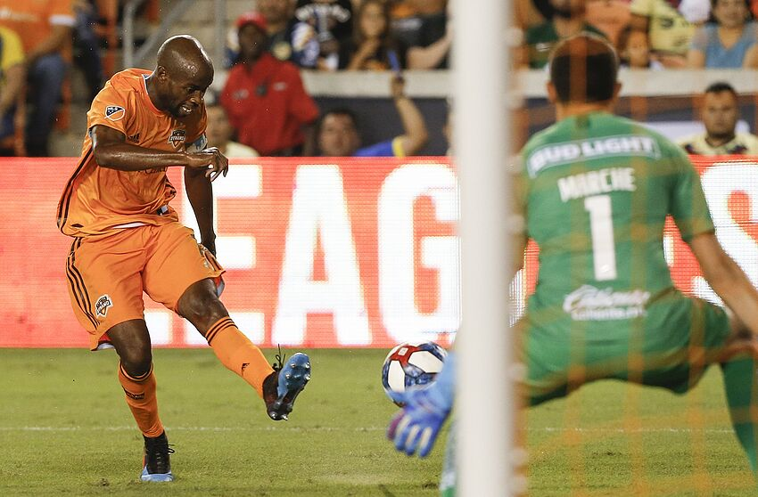HOUSTON, TEXAS - JULY 24: DaMarcus Beasley #7 of Houston Dynamo scores the equalizer in the second half as he shoots past Agustin Marchesin #1 of Club America during a quarterfinal 2019 Leagues Cup match between Club America and Houston Dynamo at BBVA Stadium on July 24, 2019 in Houston, Texas. (Photo by Bob Levey/Getty Images)