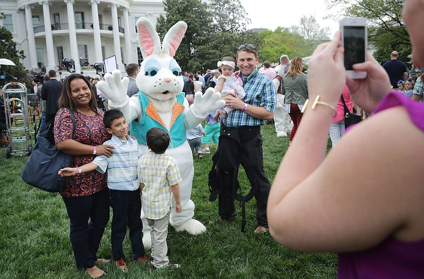 WASHINGTON, DC - APRIL 17: Families pose for photographs with one of the costumed Easter Bunny characters during the 139th Easter Egg Roll on the South Lawn of the White House April 17, 2017 in Washington, DC. The White House said 21,000 people are expected to attend the annual tradition of rolling colored eggs down the White House lawn that was started by President Rutherford B. Hayes in 1878. (Photo by Chip Somodevilla/Getty Images)