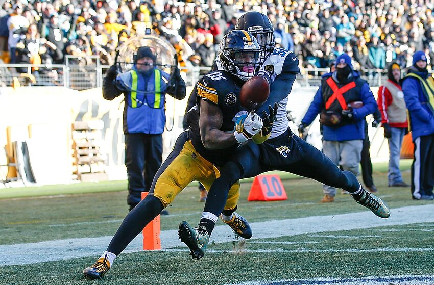 262fcc91 PITTSBURGH, PA – JANUARY 14: Le'Veon Bell #26 of the Pittsburgh Steelers  catches a landing pass towards Telvin Smith #50 of the Jacksonville Jaguars  in the ...