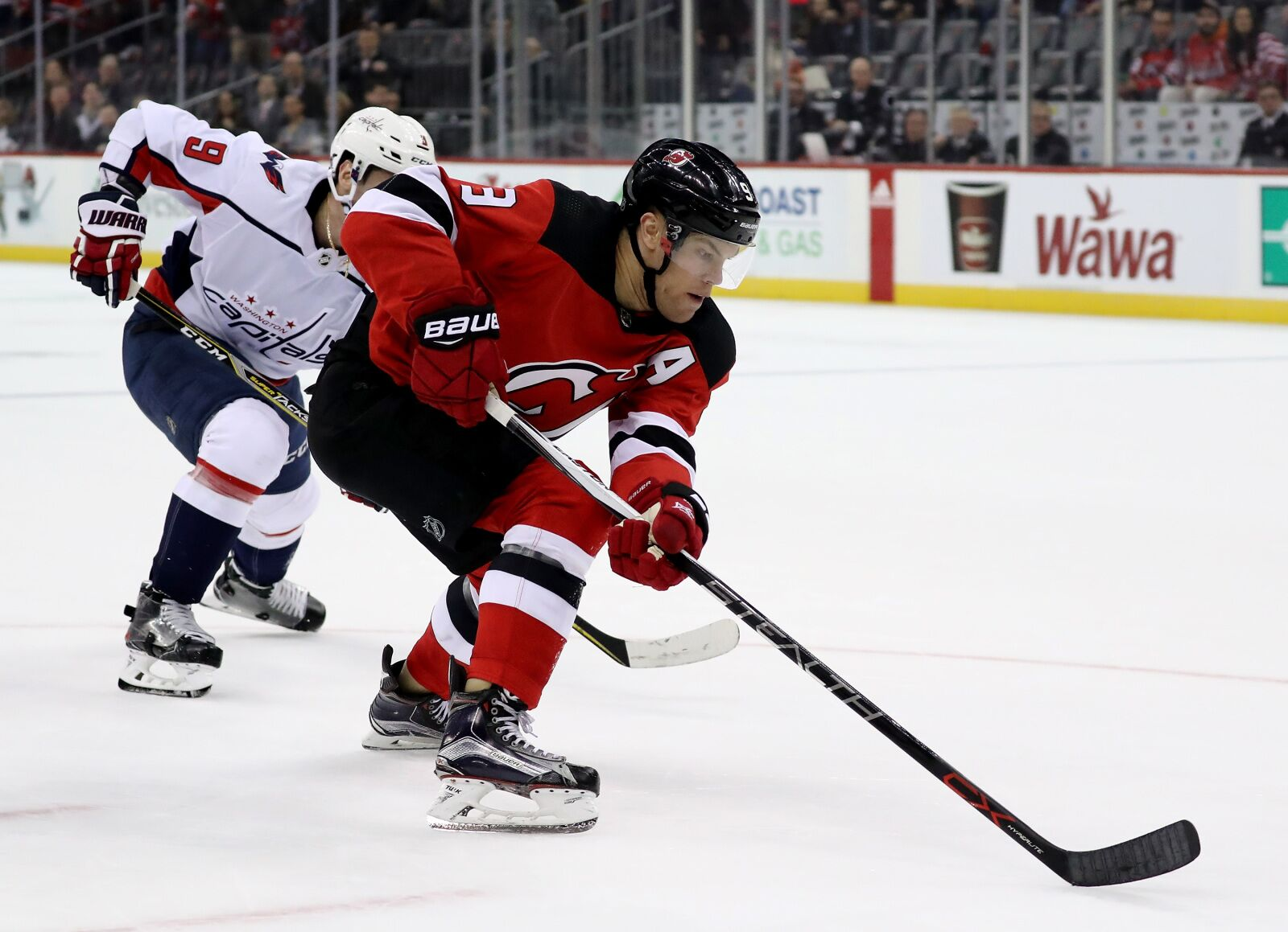 NEWARK, NJ - JANUARY 18: Taylor Hall #9 of the New Jersey Devils heads for the net and scores the game winning goal as Dmitry Orlov #9 of the Washington Capitals defends in the overtime period on January 18, 2018 at Prudential Center in Newark, New Jersey.The New Jersey Devils defeated the Washington Capitals 4-3 in overtime. (Photo by Elsa/Getty Images)