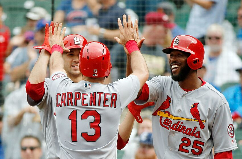 CHICAGO, IL - JULY 20: Matt Carpenter #13 of the St. Louis Cardinals is congratulated by Dexter Fowler #25 (R) and Jack Flaherty #32 (L) after hitting a three run home run against the Chicago Cubs during the sixth inning at Wrigley Field on July 20, 2018 in Chicago, Illinois. This was Carpenter's third home run of the game. (Photo by Jon Durr/Getty Images)