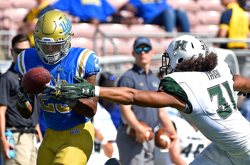 PASADENA, CA - SEPTEMBER 09: Nate Starks #23 of the UCLA Bruins hangs on to the ball to complete a 39 yard pass play before he is stopped by Jahlani Tavai #31 of the Hawaii Warriors in the first half of the game at the Rose Bowl on September 9, 2017 in Pasadena, California. (Photo by Jayne Kamin-Oncea/Getty Images)
