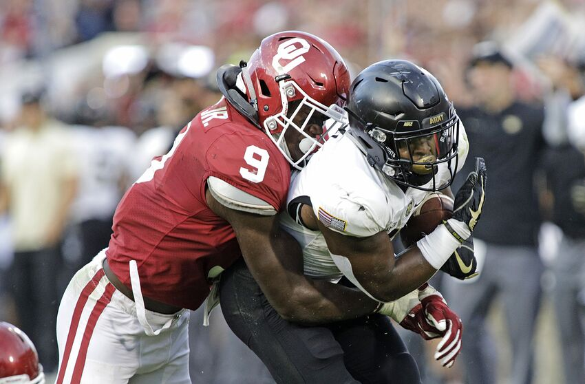 NORMAN, OK - SEPTEMBER 22: running back Kell Walker #5 of the Army Black Knights is hit by linebacker Kenneth Murray #9 of the Oklahoma Sooners at Gaylord Family Oklahoma Memorial Stadium on September 22, 2018 in Norman, Oklahoma. The Sooners defeated the Black Knights 28-21 in overtime. (Photo by Brett Deering/Getty Images)