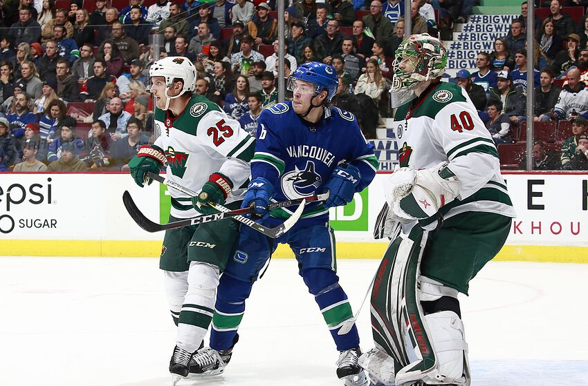 VANCOUVER, BC - DECEMBER 4: Jonas Brodin #25 of the Minnesota Wild and Brock Boeser #6 of the Vancouver Canucks stand in front of Devan Dubnyk #40 of the Minnesota Wild during their NHL game at Rogers Arena December 4, 2018 in Vancouver, British Columbia, Canada. (Photo by Jeff Vinnick/NHLI via Getty Images)