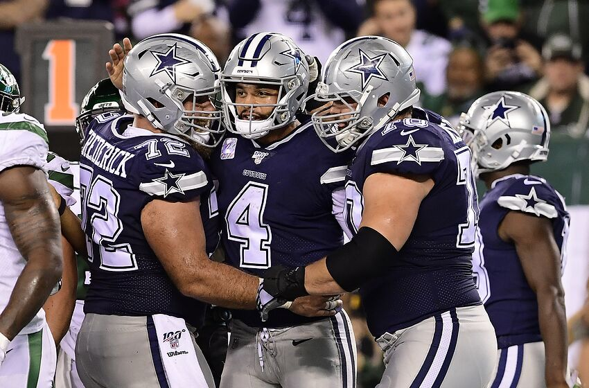 EAST RUTHERFORD, NEW JERSEY - OCTOBER 13: Dak Prescott #4 of the Dallas Cowboys is congratulated by his teammates Travis Frederick #72 and Zack Martin #70 after scoring a rushing touchdown against the New York Jets during the fourth quarter at MetLife Stadium on October 13, 2019 in East Rutherford, New Jersey. (Photo by Steven Ryan/Getty Images)
