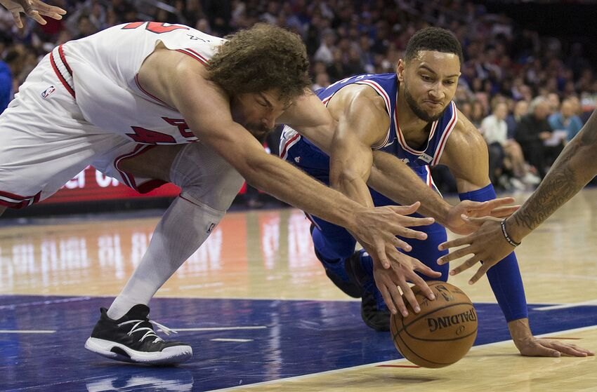 PHILADELPHIA, PA - OCTOBER 18: Robin Lopez #42 of the Chicago Bulls Ben Simmons #25 of the Philadelphia 76ers dive for the ball in the third quarter at Wells Fargo Center on October 18, 2018 in Philadelphia, Pennsylvania. The 76ers defeated the Bulls 127-108. NOTE TO USER: User expressly acknowledges and agrees that, by downloading and or using this photograph, User is consenting to the terms and conditions of the Getty Images License Agreement. (Photo by Mitchell Leff/Getty Images)