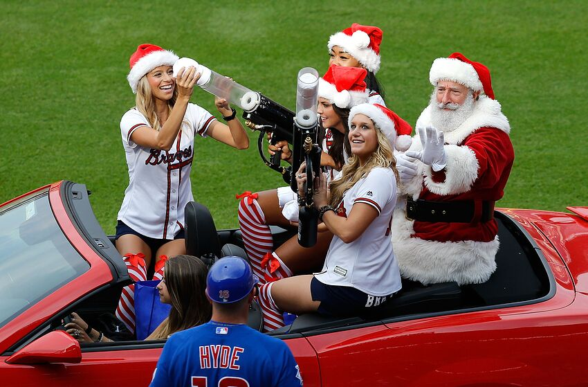 ATLANTA, GA - JULY 19: A man dressed in a Santa Claus outfit, in a car driven by Braves cheerleaders, waves to first base coach Brandon Hyde #16 of the Chicago Cubs during