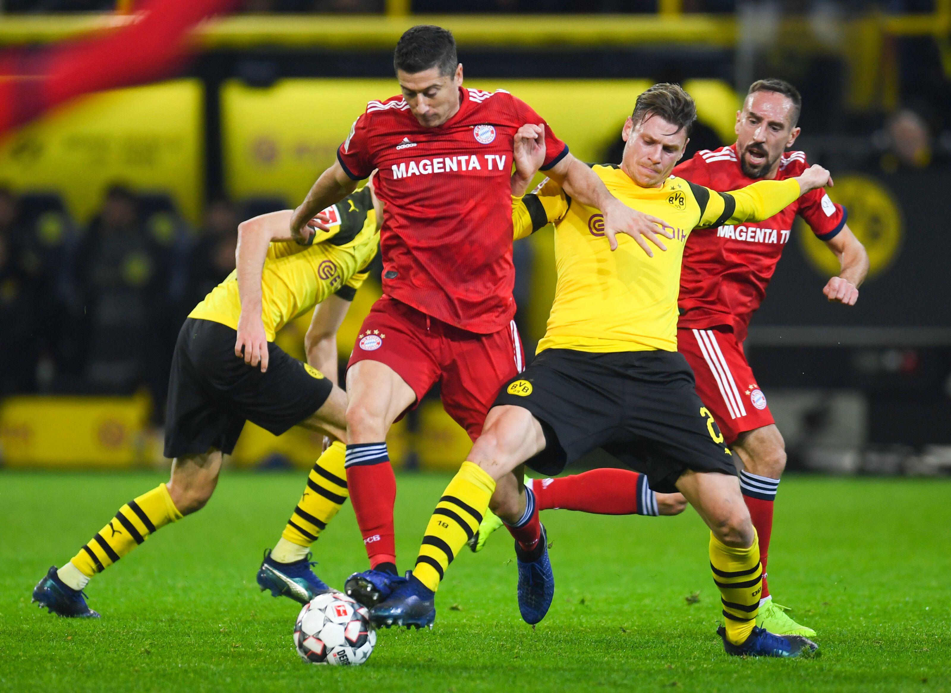 Bayern Munichs Polish Forward Robert Lewandowski And Dortmunds Polish Defender Lukasz Piszczek Vie For The Ball During The German First Division