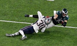 Duron Harmon of the New England Patriots tackles Zach Ertz of the Philadelphia Eagles.