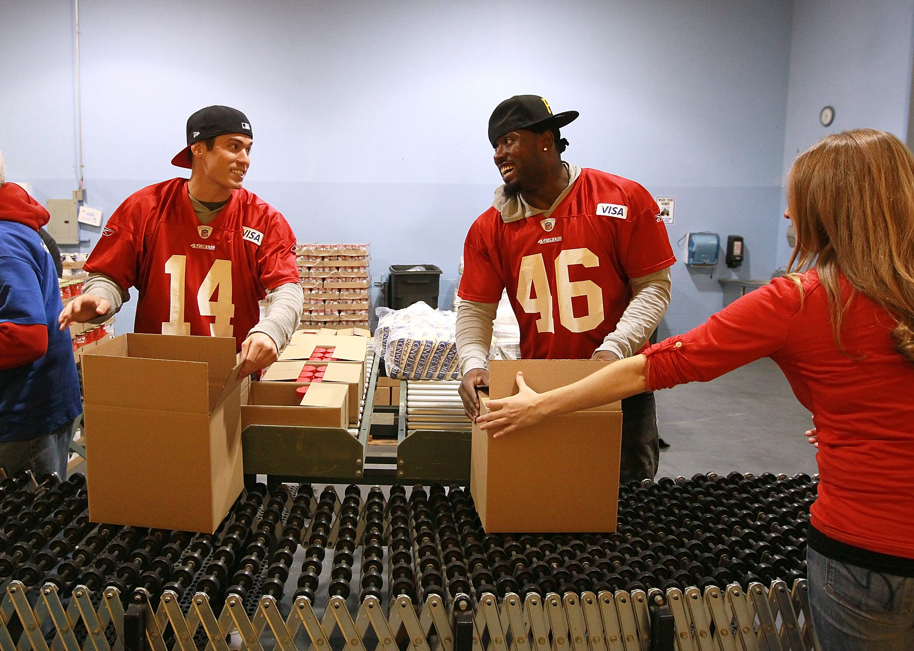 106655903-members-of-the-49ers-help-sort-and-pack-food-donations-for-the-needy.jpg