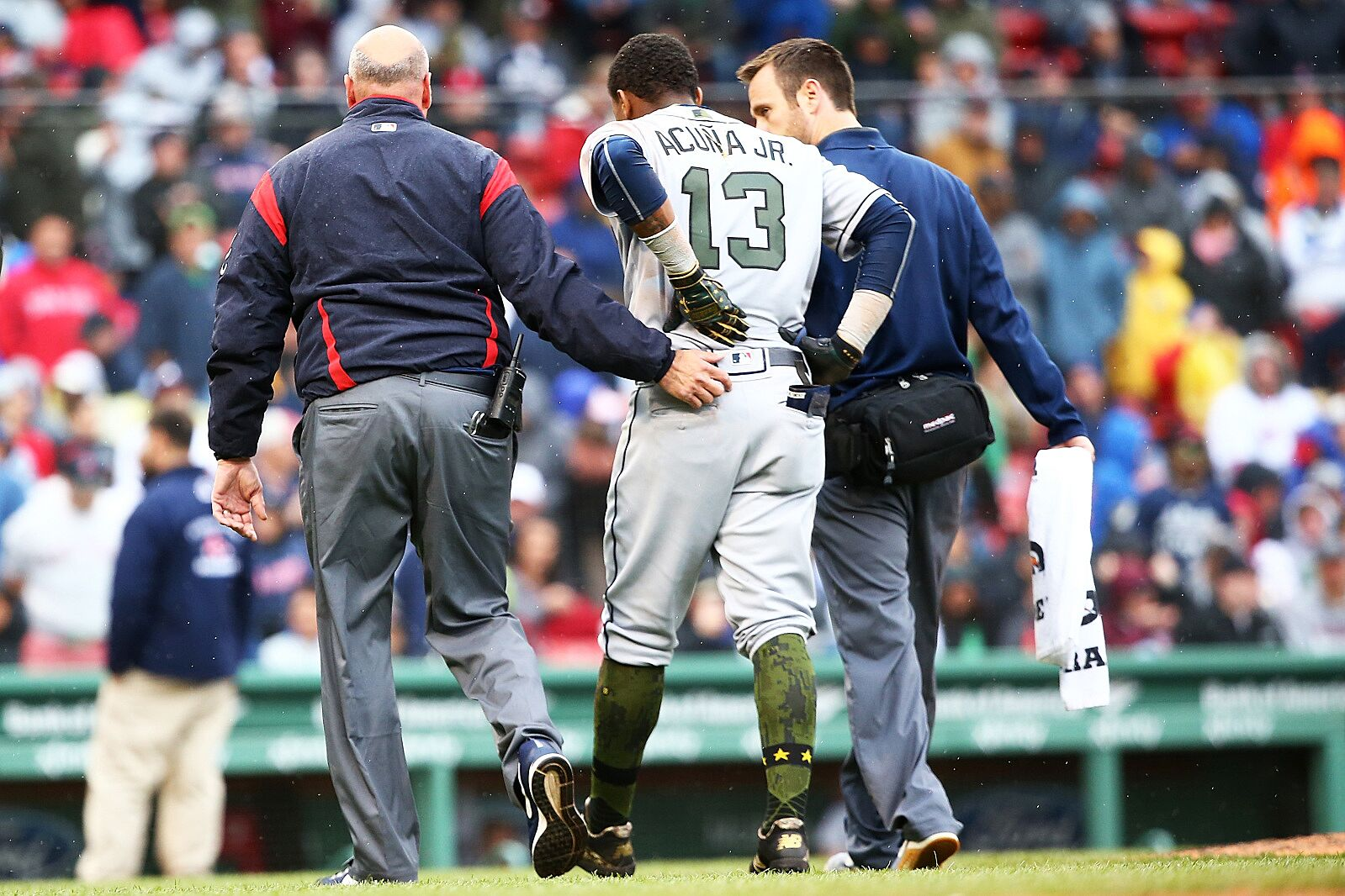 Ronald Acuna Jr. #13 of the Atlanta Braves is helped off the field after an injury at first base in the seventh inning of a game against the Atlanta Braves at Fenway Park on May 27, 2018 in Boston, Massachusetts