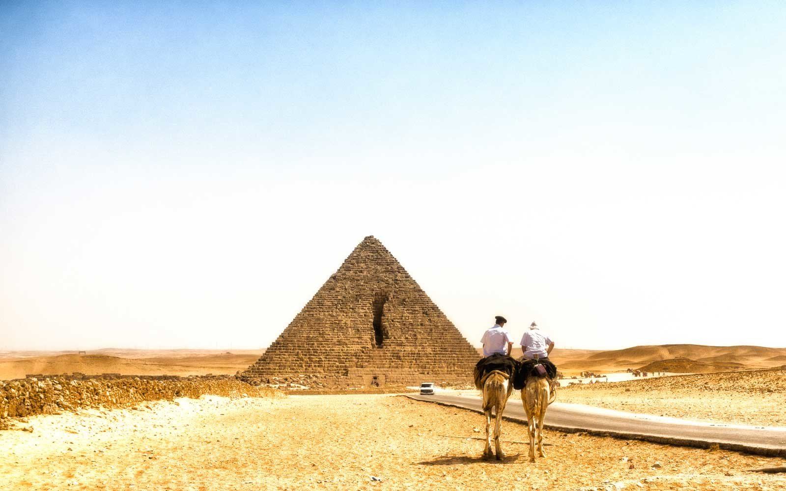 Two policemen on camels in front of the Pyramids in Giza, Egypt