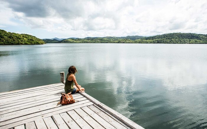 A Woman Sitting On Remote Wooden Dock Overlooking Lake