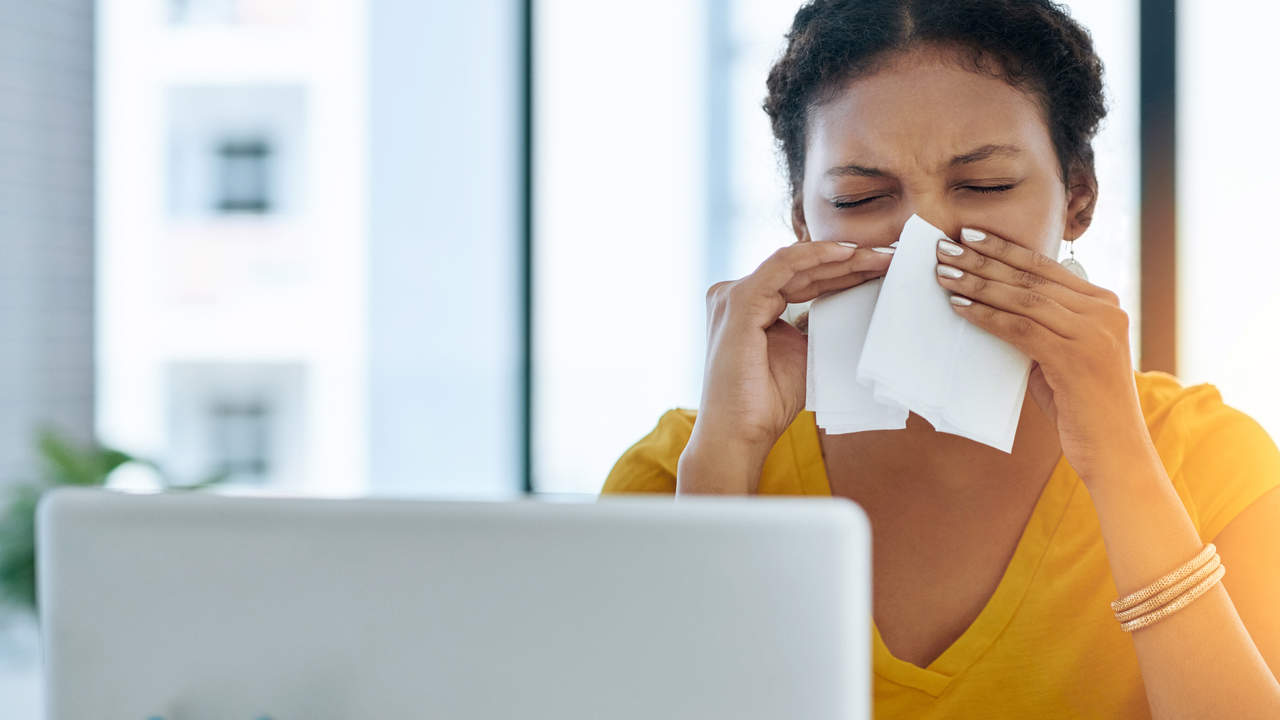 Woman blowing nose from allergies with watery eyes