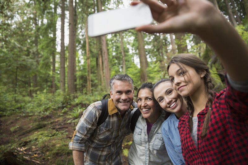 Family taking selfie while hiking in the forest