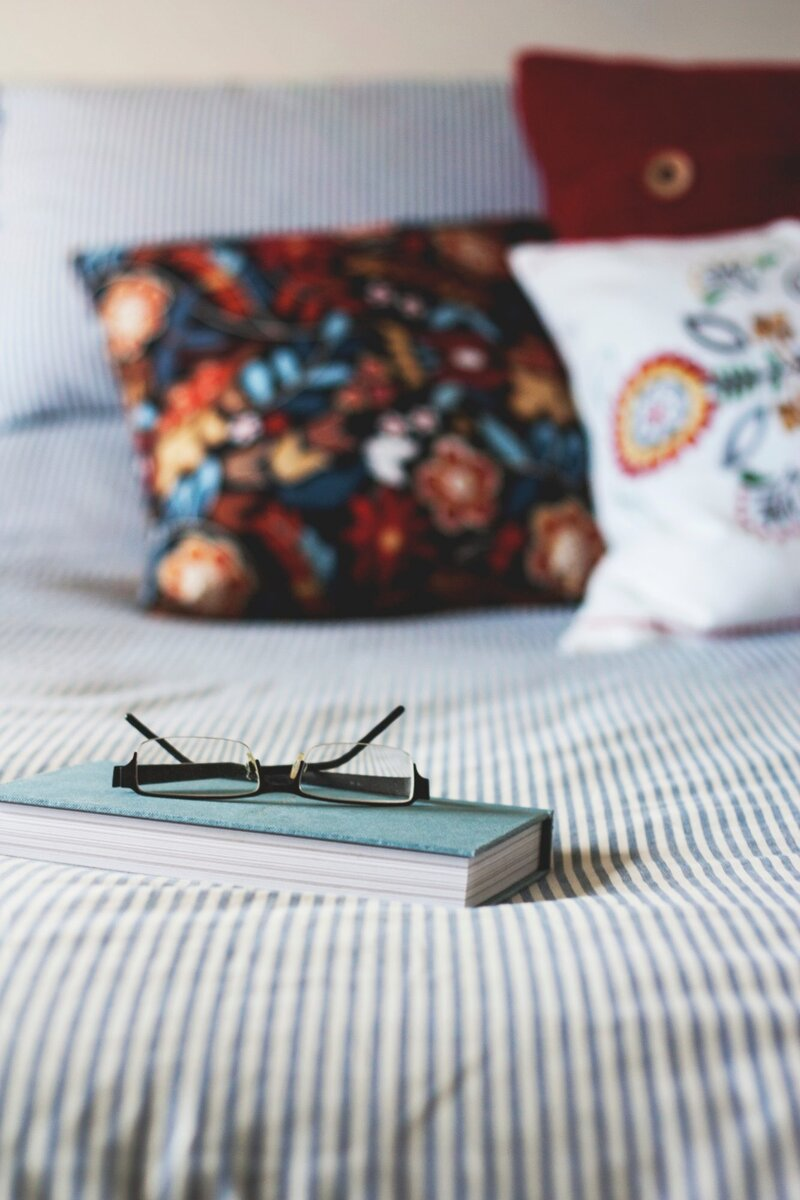 Book and reading glasses on cozy bed with pillows
