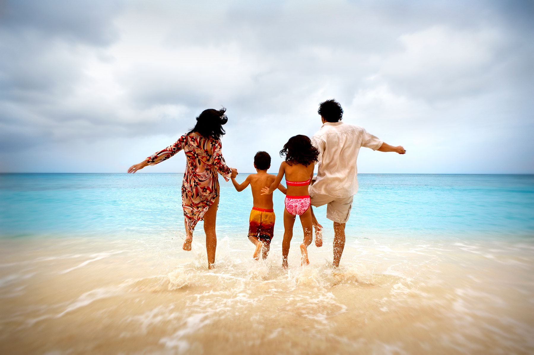 Family jumping into ocean