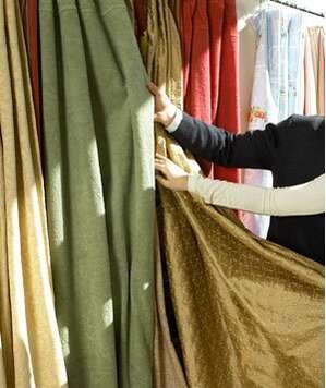 Hands selecting curtain fabric