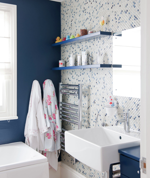 Bathroom with one navy wall and one blue and white mosaic tile wall