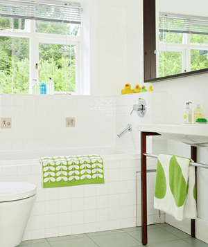 White bathroom with green accents and oversized wood-framed mirror