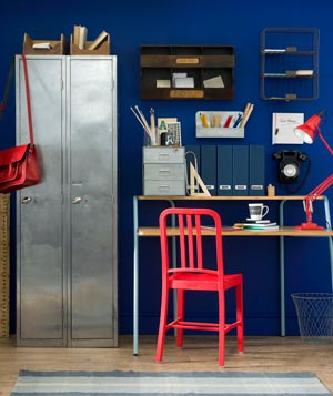 Home office space with navy walls and red accents