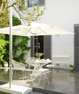 White Table Chairs And Parasol On Outdoor Patio