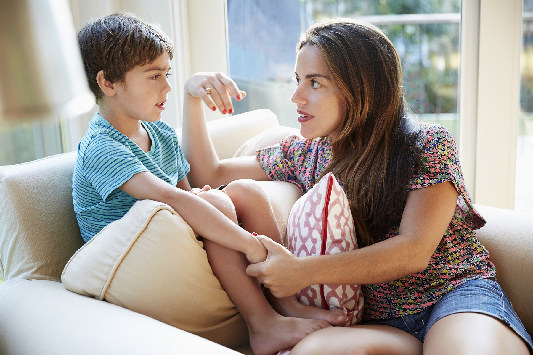Mom talking to son on sofa