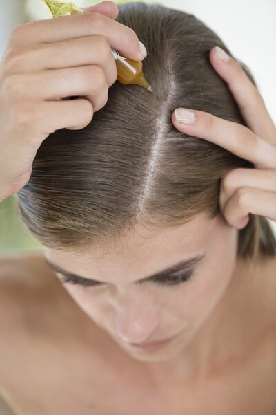 Woman putting oil on scalp