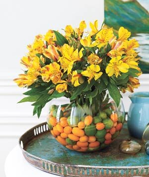 Citrus fruit and Peruvian lillies in a glass fish bowl flower arrangement