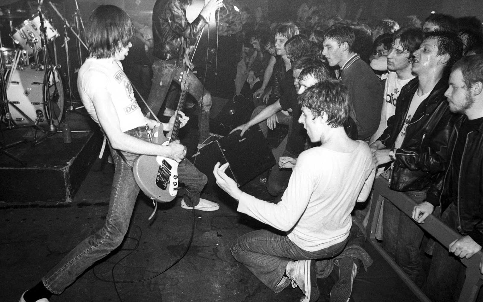 Punk fans in the audience crowd over the front of the stage and play air guitar as Joey Ramone and Johnny Ramone of The Ramones perform at Eric's club, Liverpool, 19 May 1977.